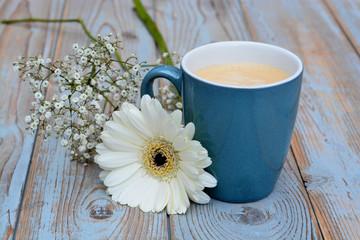 blauwe koffiekop met witte gerbera en gipskruid op oud hout