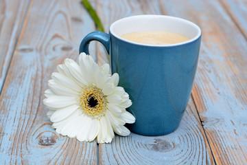 blauwe koffiekop met witte gerbera op oud hout