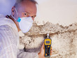 Pest controler gauges a mold infestation - 71270129