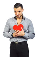 Young handsome man holding a red heart shaped toy