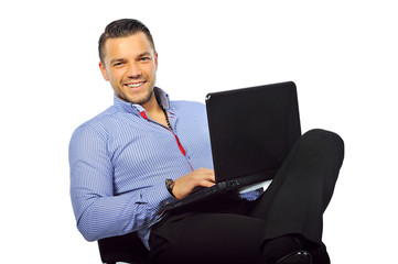Happy smiling young man sitting at studio with laptop computer i