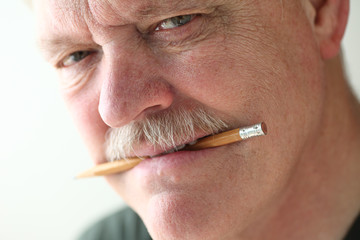 Older man with pencil between his teeth