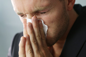 young businessman is sneezing with toilet paper