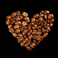 Valentine day heart from coffee beans on black