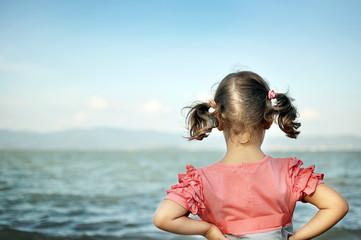Bambina di spalle che guarda il mare