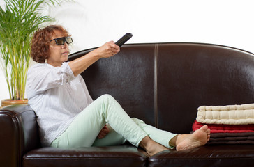 a woman of mature age  watch TV with  3D glasses