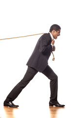 African businessman pulling a rope on white background