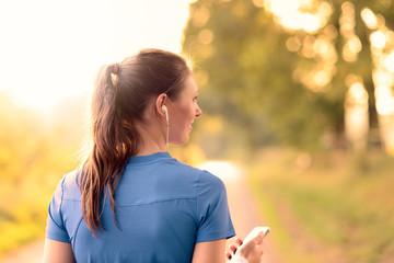 Junge Frau mit Smartphone hört Musik, Rückansicht