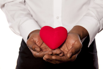 young dark-skinned man holding a heart shape object