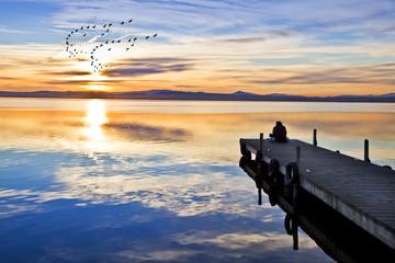 gente en el embarcadero mirando el amanecer
