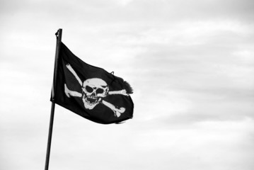 Torn Jolly Roger flies from flagpole