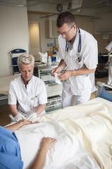 Nurses preparing an iv for the patient.