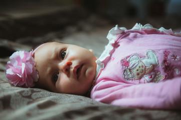 Image of cute little girl in pink suit indoor. Newborn baby