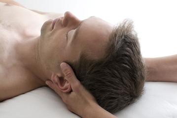 Masseurin hält Kopf in Entspannungslage