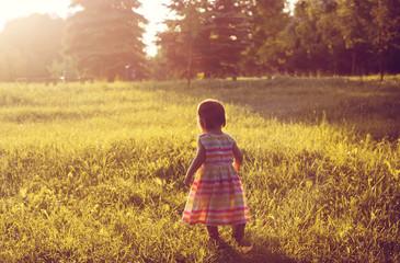 Little girl on a yellow summer field