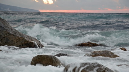 Sea waves with splashes break about stones early in morning
