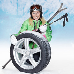 Woman with skiing gear and winter tyre