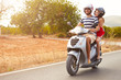 Leinwanddruck Bild - Young Couple Riding Motor Scooter Along Country Road