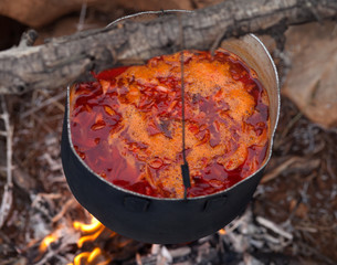 Cooking borscht (Ukrainian traditional soup) on campfire
