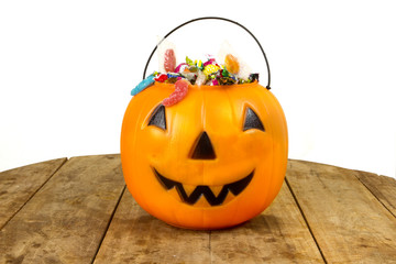 A plastic pumpkin filled with candy wooden table