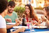 Fototapety Group Of Young Friends Enjoying Meal In Outdoor Restaurant