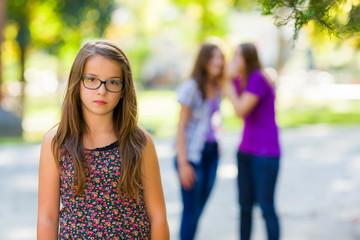 Sad girl in front of her evil girlfriends