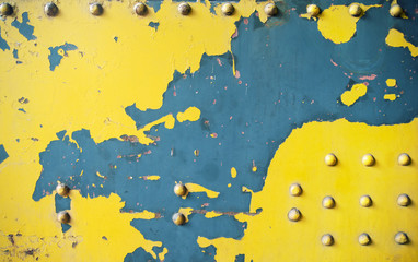Scratched yellow wall made of metal