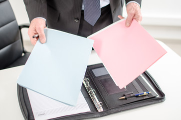 Businessman holding folders in his hands