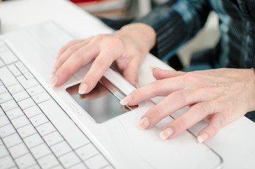 Female hands working on a laptop computer keyboard
