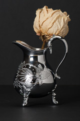 Dried Rose In Old Silver Pitcher With Decorative Stamping Patter