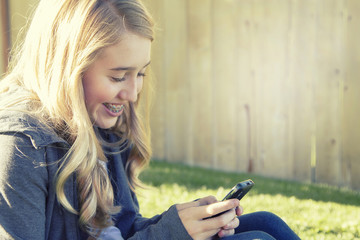 Teenage girl smiling while using a cell phone