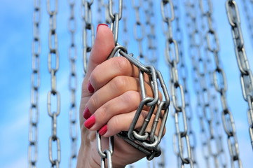 Female hand in metal chains against the blue sky