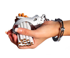 Cigarettes and handcuffs on female hand isolated