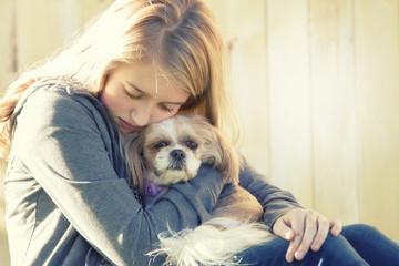 A sad or depressed teenage girl hugging a small dog