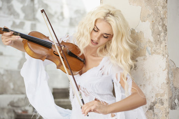 Blond cute woman playing violin