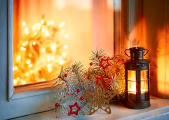 Christmas lantern in night on old window.