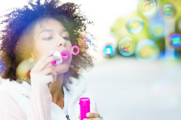 Afro woman blowing soap bubbles outdoors