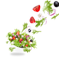 Fresh salad with flying vegetables ingredients isolated on a whi