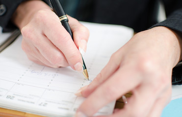 Businesswoman noting an appointment in her diary