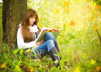 Девушка читает книгу в парке возле дерева