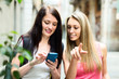 Two nice girls finding path with smartphone