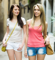 female friends in shorts having city tour at vacation