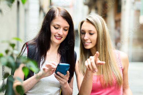 canvas print picture Two nice girls finding path with smartphone