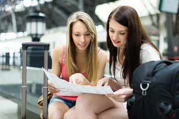 Two young women with baggage and map