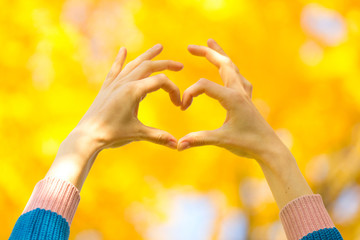 Heart symbol from fingers of hands against bright yellow autumn