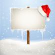 Wegweiser mit Weihnachtsmütze im Schnee