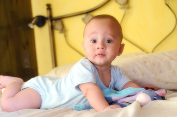 baby built on the bed looking curiously