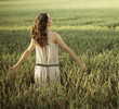 Pretty woman walking on the corn field