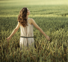 Pretty woman walking on the corn field