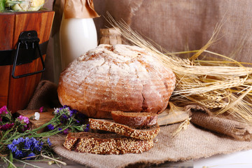 Big wooden basket, ears bread, dried flowers and milk